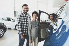 Afrikaanse Amerikaanse familie bij het autohandel drijven Vader, moeder en zoons het stellen dichtbij nieuwe auto stock afbeelding