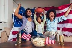Afrikaanse Amerikaanse familie van het letten op drie TV en thuis het toejuichen van sportspelen op bank royalty-vrije stock afbeeldingen