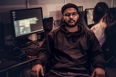 Afrikaanse Amerikaanse gebaarde kerel hoodie en GLB-zitting die op een gamerstoel en een camera in een gokkenclub bekijken dragen stock foto