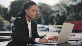 Afrikaanse Amerikaanse jonge vrouw die aan de laptop zittingszitting werken in koffie op het de zomerterras Zaken, het werken stock video