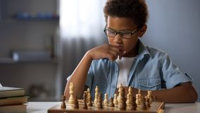 Afrikaanse Amerikaanse jongen die logisch gezien uit strategie van het spelen schaak denken, hobby stock foto