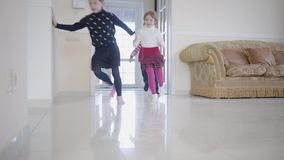 Afrikaanse Amerikaanse jongen en twee meisjes die in het huis spelen Drie gelukkige jonge geitjes openen de deur en stellen binne stock footage