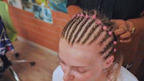 Afrikaanse Amerikaanse kappercoiffeur weeft Franse vlechten, het kapsel van de bruid stock videobeelden