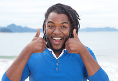 Afrikaanse Amerikaanse kerel met dreadlocks die aan muziek bij strand luisteren Royalty-vrije Stock Foto's