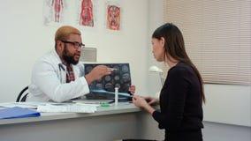 Afrikaanse Amerikaanse mannelijke arts die hersenen gegevens verwerkte tomografie verklaren aan vrouwelijke patiënt stock video