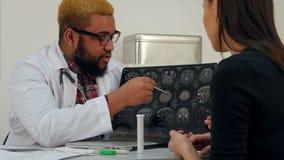 Afrikaanse Amerikaanse mannelijke arts die hersenen xray beeld verklaren aan vrouwelijke patiënt stock footage