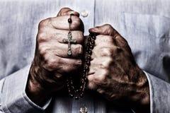 Afrikaanse Amerikaanse mannelijke handen die houdend een parelsrozentuin met Jesus Christ in het kruis of het Kruisbeeld bidden royalty-vrije stock afbeeldingen