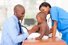 Het pediatrische arts onderzoeken Stock Afbeeldingen