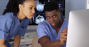Afrikaanse Amerikaanse medische specialisten die computers met behulp van Royalty-vrije Stock Foto's