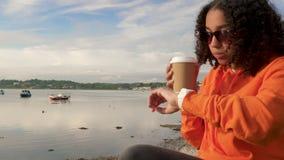 Afrikaanse Amerikaanse meisjestiener gebruikend slim horloge en drinkend koffie stock video