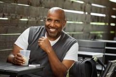 Afrikaanse Amerikaanse mens bij een en koffie die drinken texting Stock Afbeelding