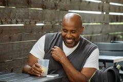 Afrikaanse Amerikaanse mens bij een en koffie die drinken texting Royalty-vrije Stock Afbeeldingen