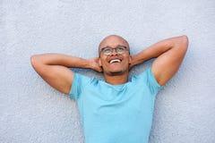 Afrikaanse Amerikaanse mens die met glazen glimlachen die omhoog in overpeinzing kijken Stock Foto