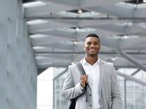 Afrikaanse Amerikaanse mens die met zak bij luchthaven glimlachen royalty-vrije stock fotografie