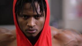 Afrikaanse Amerikaanse mens die oefening op opleidingsapparaten maken in gymnastiek stock footage