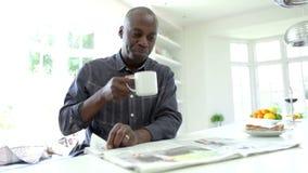 Afrikaanse Amerikaanse Mens die Ontbijt eten en Krant lezen stock video