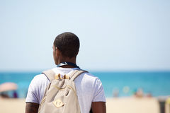 Afrikaanse Amerikaanse mens die zich bij het strand met zak bevinden Stock Fotografie
