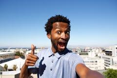 Afrikaanse Amerikaanse mens die zich door stedelijke achtergrond met omhoog duim bevinden royalty-vrije stock afbeelding