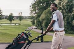 Afrikaanse Amerikaanse mens die in zonnebril met zakhoogtepunt lopen van golfclubs Royalty-vrije Stock Fotografie