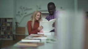 Afrikaanse Amerikaanse mens en Europees meisje die een boek in de bibliotheek wegknippen stock video