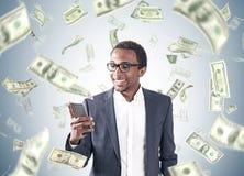 Afrikaanse Amerikaanse mens, smartphone, dollarregen Stock Foto's