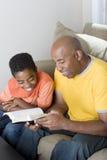 Afrikaanse Amerikaanse mensenlezing met zijn zoon royalty-vrije stock afbeeldingen
