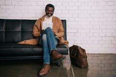 Afrikaanse Amerikaanse mensenzitting bij luchthaven en het kijken stock afbeelding