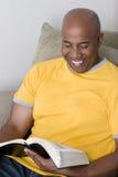 Afrikaanse Amerikaanse mensenzitting op een bank en lezing stock afbeelding
