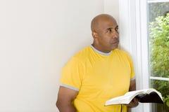 Afrikaanse Amerikaanse mensenzitting op een bank en lezing royalty-vrije stock foto