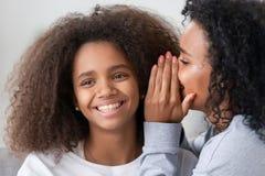 Afrikaanse Amerikaanse moeder die aan het glimlachen van het oor van de tienerdochter fluisteren stock afbeelding