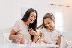 Afrikaanse Amerikaanse moeder die gelukkige dochter bekijken die manicure doen Stock Fotografie