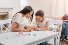 Afrikaanse Amerikaanse moeder en dochter die manicure thuis doen Royalty-vrije Stock Foto's