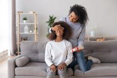 Afrikaanse Amerikaanse moeder sluitende ogen die van tienerdochter, verrassing voorbereiden stock afbeelding