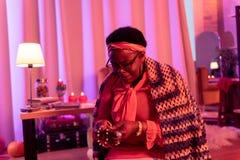 Afrikaanse Amerikaanse mollige waarzegger die met grote ringen het koord van parels bekijken stock fotografie