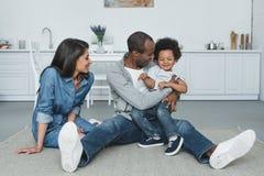 Afrikaanse Amerikaanse ouders die pret met zoon op vloer hebben stock fotografie