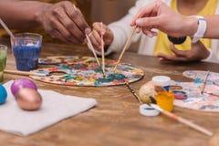 Afrikaanse Amerikaanse ouders en dochter die verfborstels op palet, Pasen-concept zetten Royalty-vrije Stock Afbeelding
