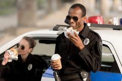 Afrikaanse Amerikaanse politieagent die met document kop van koffie hamburger eten terwijl zijn vrouwelijke partner die hamburger royalty-vrije stock fotografie