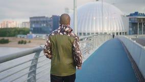 Afrikaanse Amerikaanse professionele sportman die op stedelijke brug sprinten stock video