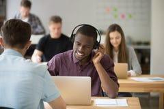 Afrikaanse Amerikaanse raadplegende cliënt die draadloze hoofdtelefoon met behulp van royalty-vrije stock foto's