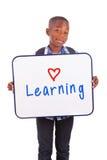 Afrikaanse Amerikaanse schooljongen die een lege raad houden - Zwarte mensen Stock Foto