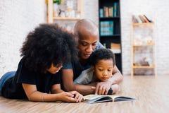 Afrikaanse Amerikaanse vader die een verhaal van de sprookjemythe voor jong geitje lezen royalty-vrije stock afbeelding