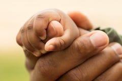 Afrikaanse Amerikaanse vader die zijn dochtershanden houden Stock Fotografie