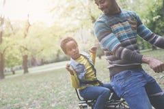 Afrikaanse Amerikaanse vader die zijn meisje op fiets drijven stock fotografie