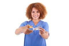Afrikaanse Amerikaanse verpleegster die een sigaret met schaar snijden - Bla Royalty-vrije Stock Foto's