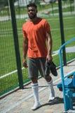 Afrikaanse Amerikaanse voetballer die langs voetbalhoogte lopen Stock Foto's