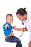 Afrikaanse Amerikaanse vrouw arts met kind stock foto