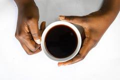 Afrikaanse Amerikaanse vrouw beide handen die een witte kop van koffie houden Zwarte Vrouwelijke handen die een hete kop van koff stock afbeelding