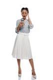 Afrikaanse Amerikaanse vrouw die die smartphone gebruiken op wit wordt geïsoleerd Stock Afbeeldingen