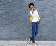 Afrikaanse Amerikaanse vrouw die en op cellphone lopen spreken Royalty-vrije Stock Afbeeldingen