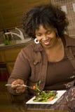Afrikaanse Amerikaanse vrouw die etend een salade glimlachen royalty-vrije stock foto's
